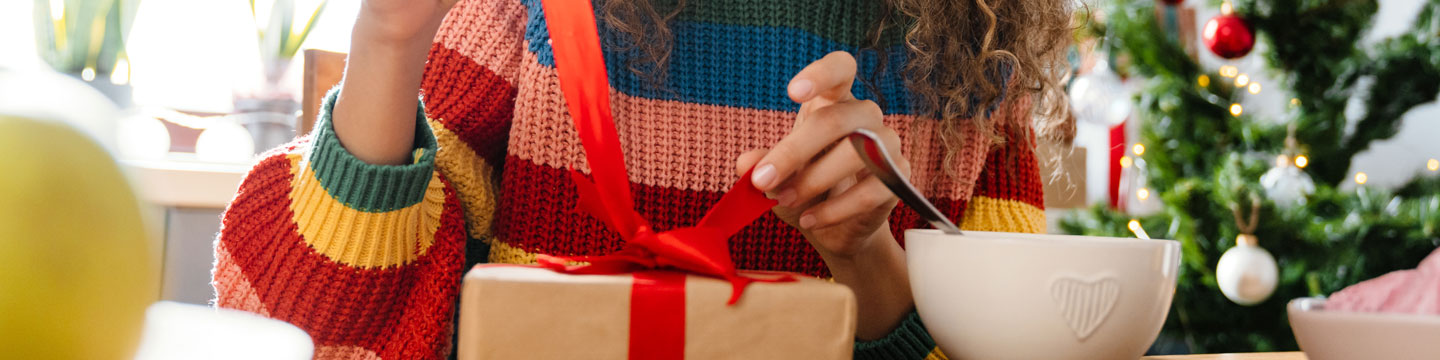 A girl opening up a holiday gift.