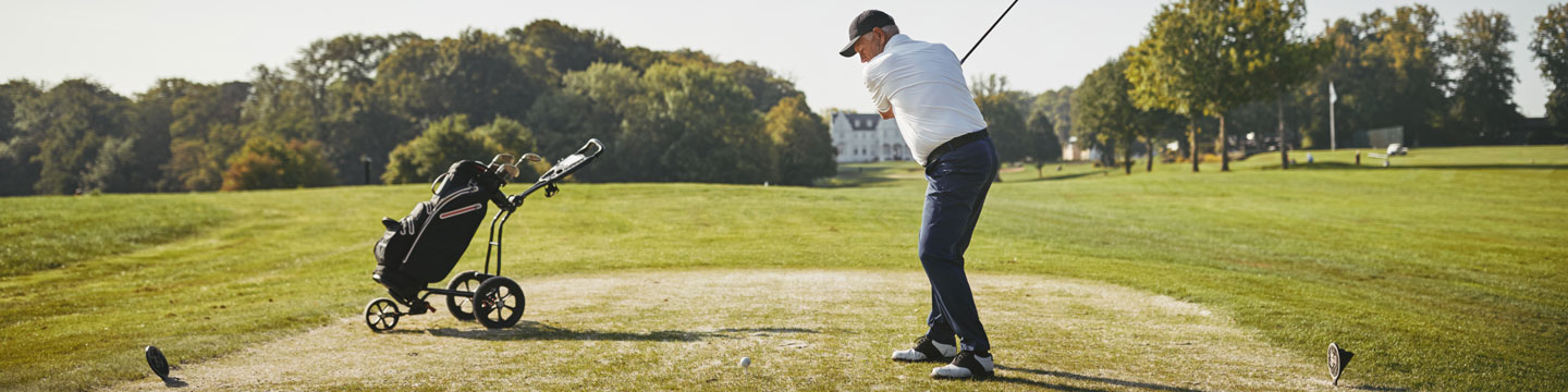 A man swinging about to hit a golf ball on a golf course.